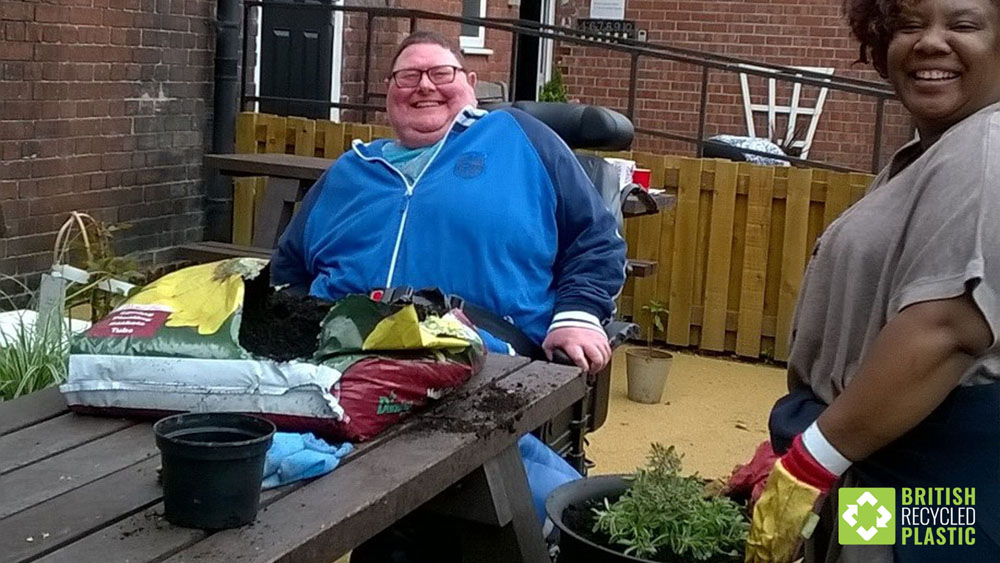 Gary using a wheelchair accessible recycled plastic table