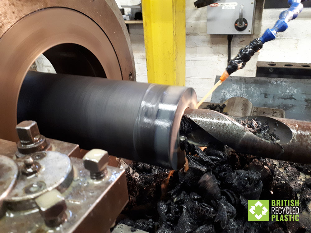 Drilling out the core of a recycled plastic bollard in preparation for a steel insert