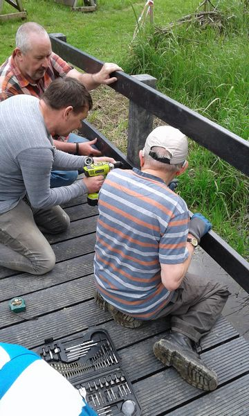 Volunteers using recycled plastic planks and posts to make a small bridge