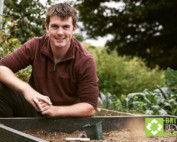 Huw Richards sitting down next to a recycled plastic raised bed