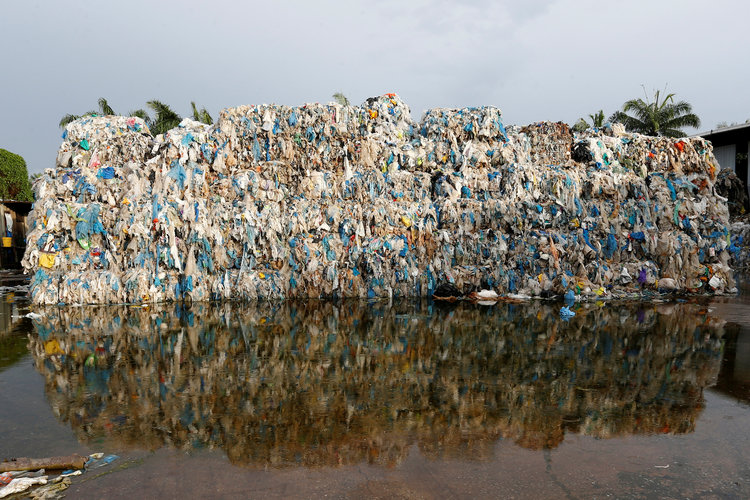 A photo of lots of bales of plastic waste imported into Asia and left to degrade.