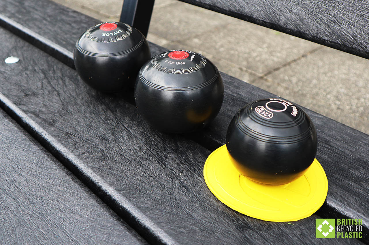 Main article photo showing crown green bowls on a recycled plastic bench