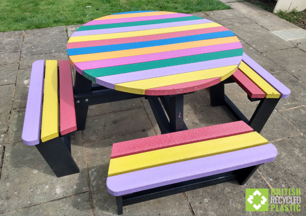 A rainbow coloured circular recycled plastic picnic table, ideal for schools