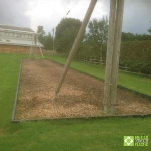 Recycled plastic lumber planks used to retain woodchip in a zipline pit.