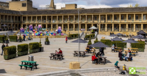 Various Denholme picnic tables at The Piece Hall, with visitors 02