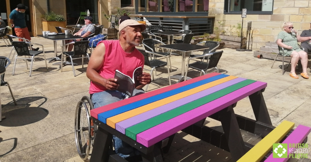 Krishna Francis at a Bradshaw wheelchair-accessible picnic table engineered from British Recycled Plastic