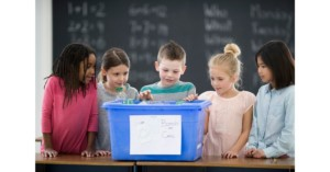 Teaching sustainability to kids in a classroom with recycling bins