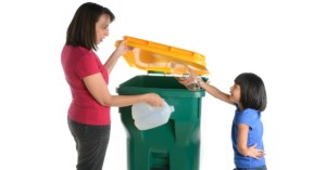 Parent teaching sustainability to kids with recycling bin
